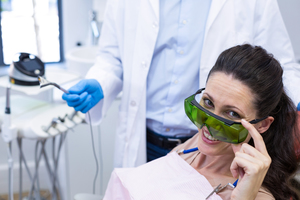 Dental patient looks over goggles and smiles